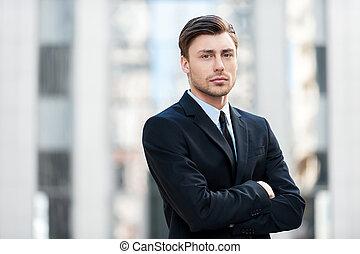 serio, businessman., pensativo, joven, en, formalwear, mantener, armamentos cruzaron, y, mirar cámara del juez