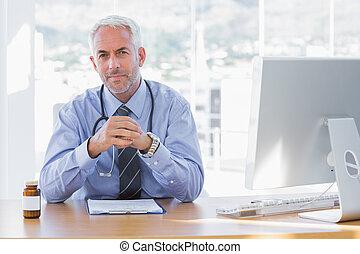 serio, doctor, sentado, en, el suyo, escritorio