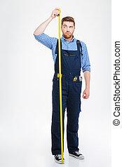 serio, joven, trabajador, posición, y, medición, el suyo, crecimiento, con, cinta