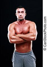 serio, muscular, hombre, con, brazos doblados, posición, fondo blanco