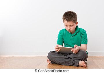 serio, niño joven, sobre el piso, ocupado, con, tableta