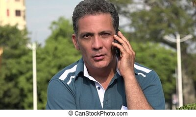 Serious Adult Hispanic Man Using Cell Phone