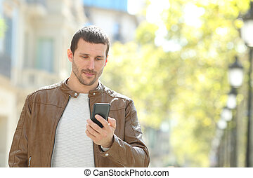 Serious adult man checking smart phone in the street
