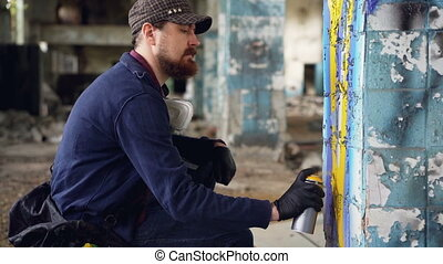 Serious adult man graffiti artist in leather gloves is...