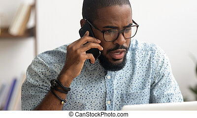 Serious African American businessman talking on phone at workplace