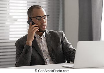 Serious African American businessman talking on phone, using laptop