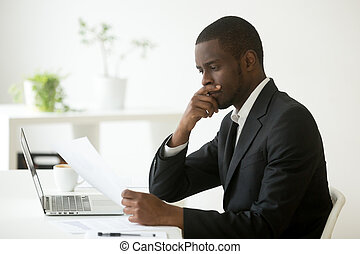 Serious african-american businessman thinking of notice reading