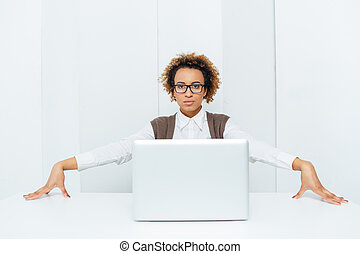 Serious african american businesswoman sitting and posing with laptop