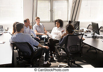African American female leader, coach talking with employees