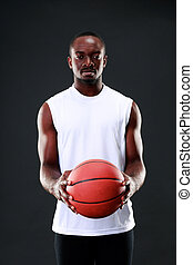 Serious african american holding  basketball ball over black background