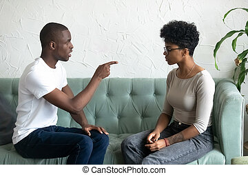 Serious African American man blaming upset woman, pointing finge