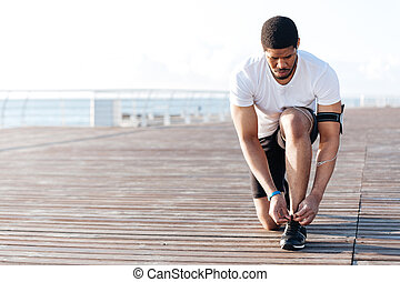 Serious african american young sportsman laces his sneakers