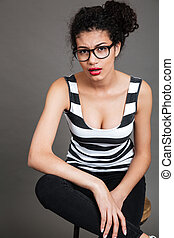 Serious african american young woman in glasses sitting on chair
