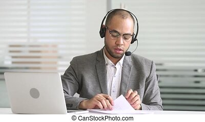Serious african american customer support service agent wearing headset talking with distant client looking at laptop making notes, mixed race businessman skyping on conference video call write information