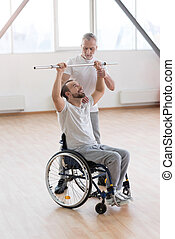 Serious aged general practitioner teaching the disabled in the gym
