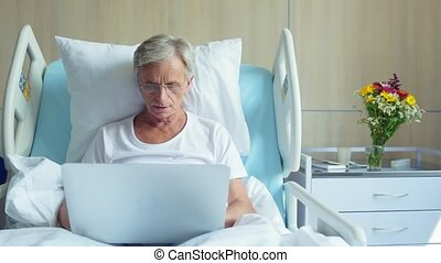 Serious aged man using laptop in the hospital - Concentrate...