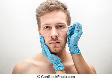 Serious and concentrated young man look straight. His face is held by woman's hands in gloves. She has syringe. Isolated on white background.