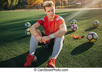Serious and concentrated young player sit on lawn and look to right. He listen to music through headphones. Guy hold phone in hands. Balls are behind him.