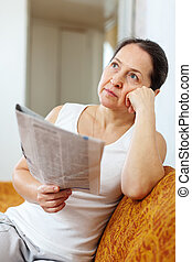 wistful mature woman with newspaper