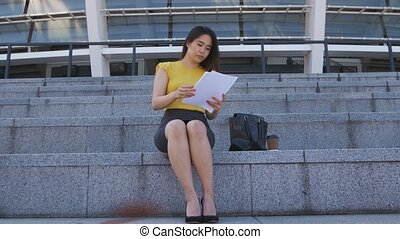 Serious asian business lady reading paperwork