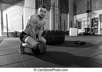 Serious athletic man putting a med ball on the floor
