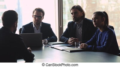 Serious attentive hr team male and female employers recruiters interviewing male job applicant seeker listening qualification performance make first impression employment decision at hiring meeting
