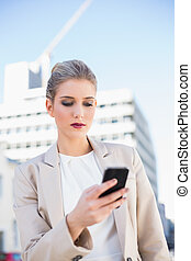Serious attractive businesswoman sending a text message