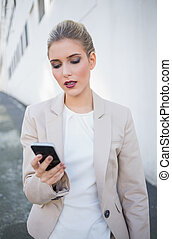 Serious attractive businesswoman sending a text