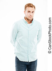 Serious attractive young man standing with hands behind back