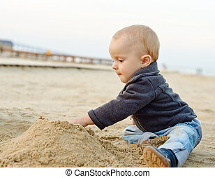 baby boy playing in sand