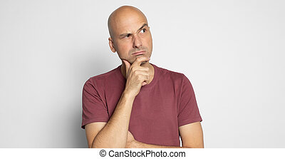 Serious bald man is thinking looking up to copy space isolated