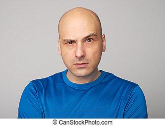 Serious bald man with raised eyebrow