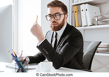 Serious bearded businessman holding pencil.