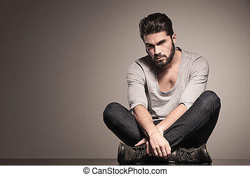 serious bearded fashion man sits in yoga position on the ...