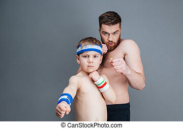 Serious bearded father and his little son punching at camera