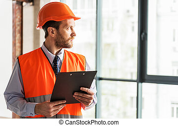 Serious bearded foreman glancing aside