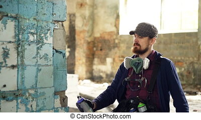 Serious bearded guy is concentrated on painting graffiti on...