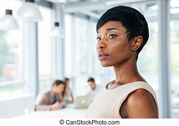 Serious beautiful african american young businesswoman standing in office