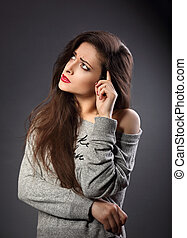 Serious beautiful woman in casual clothing looking up and thinking on dark grey background with empty copy space