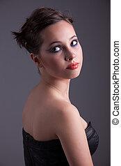 serious beautiful woman, looking back, studio shot