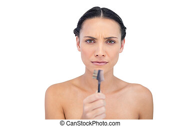 Serious beautiful young model holding eyebrow brush