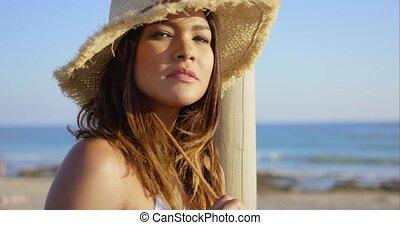 Serious beauty wearing straw hat and white bikini on beach...