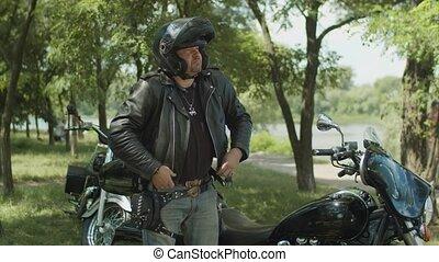 Serious biker dressing up black leather jacket - Handsome...