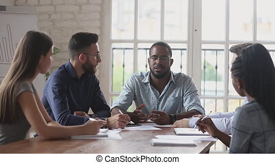 Serious black male boss explain strategy at multiracial ...