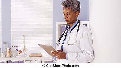 Serious Black Senior doctor standing in office with tablet