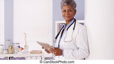 Serious Black Senior doctor working on tablet in office