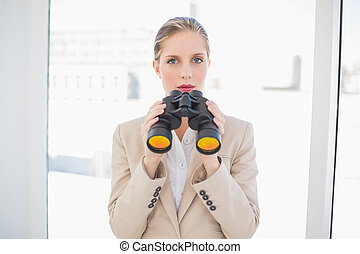 Serious blonde businesswoman holding binoculars
