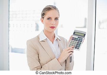 Serious blonde businesswoman showing calculator