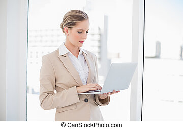 Serious blonde businesswoman using