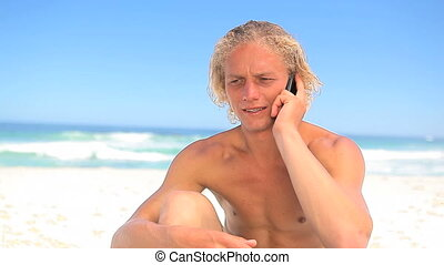 Serious blonde man using his mobile phone